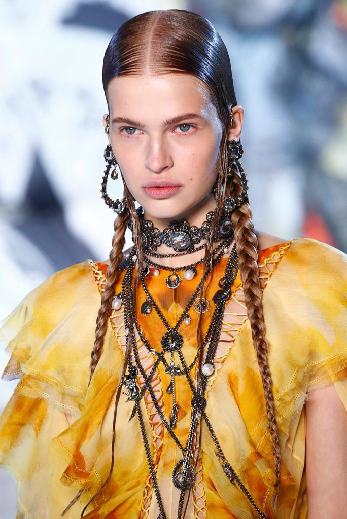 Paris Fashion Week SS19: Close up shot of a model on the Alexander Mcqueen runway with long, dark brown sleek pigtails, wearing yellow jacket with tonnes of jewellery