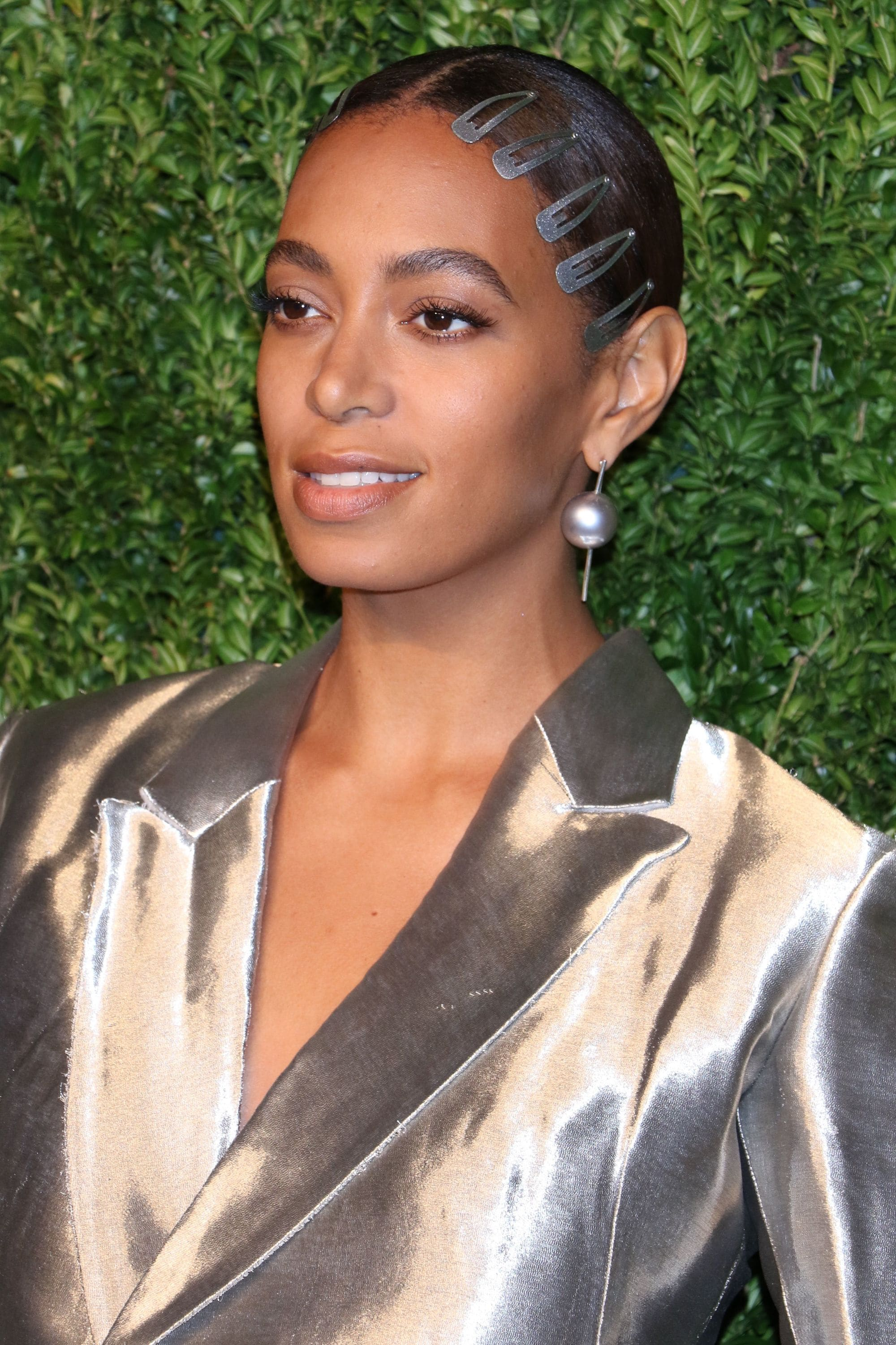 solange knowles wears brown hair in smooth back updo with hair clips along hairline and metallic blazer