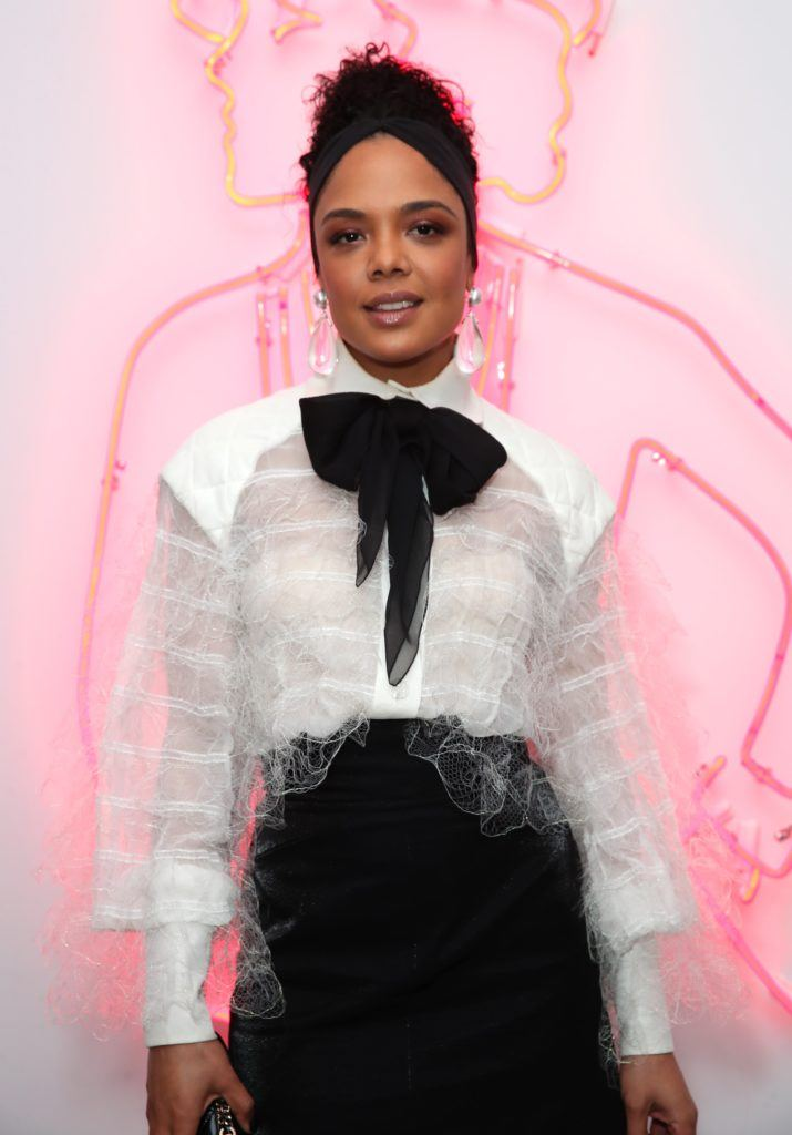 tessa thompson with dark brown hair in updo with thick black headband wearing a white shirt and big bow tie