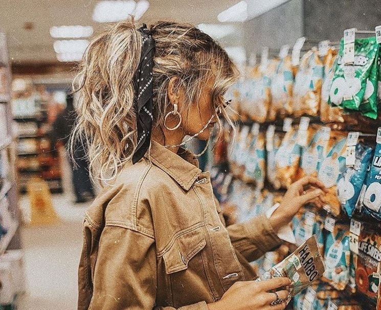 textured hairstyles: close up Instagram shot of woman in a shop, with a messy high ponytail and hair scarf, wearing all tan and sunglasses