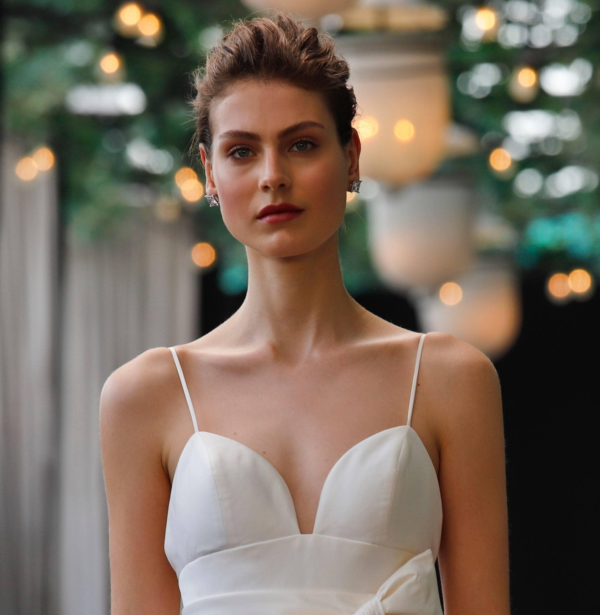 Shot of model on a bridal runway with short hair styled into a messy, swept-back quiff, wearing all white