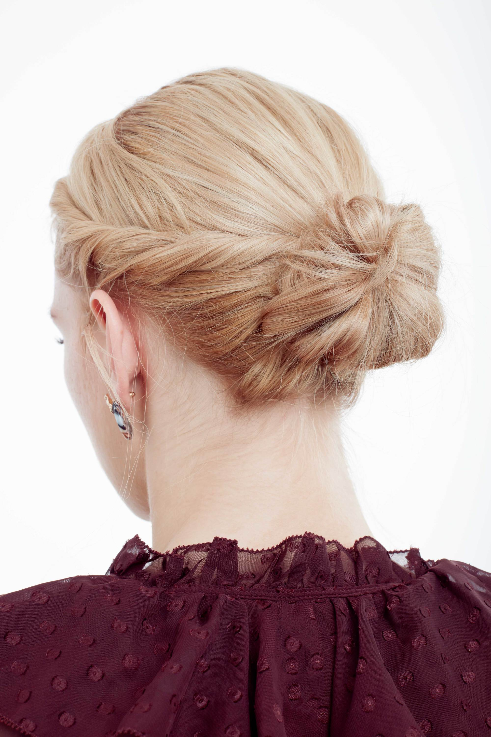 Wedding guest hair: Rear shot of model with golden blonde hair styled into a low twisted bun, wearing a ruffled purple top in the All Things Hair UK studio