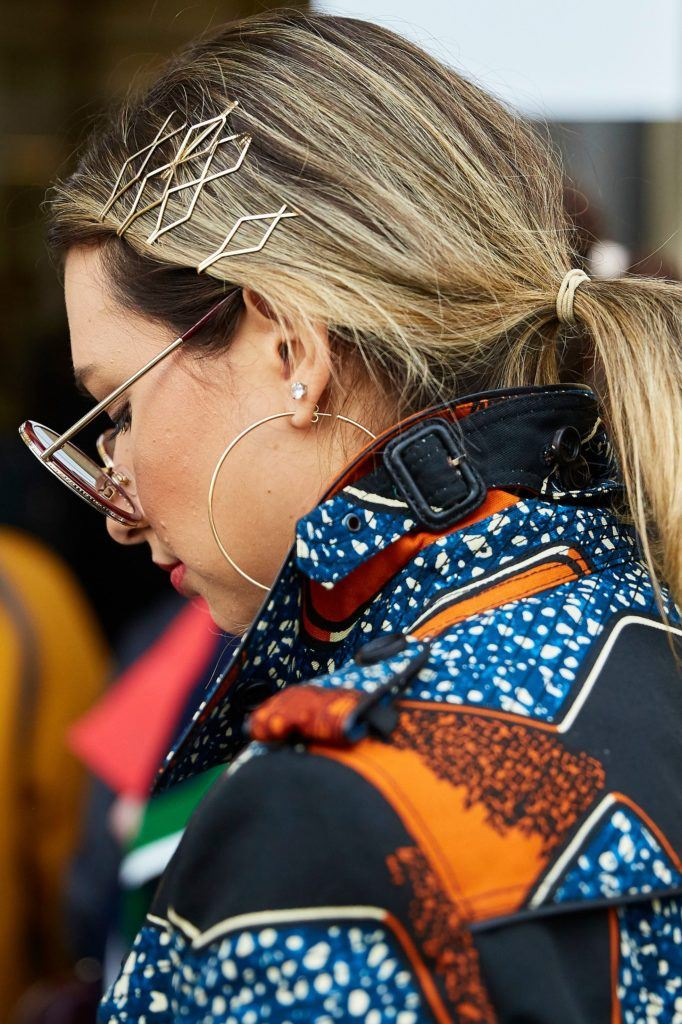 Close-up shot of a woman with blonde/brunette highlighted hair in a low ponytail with hair slides, wearing sunglasses