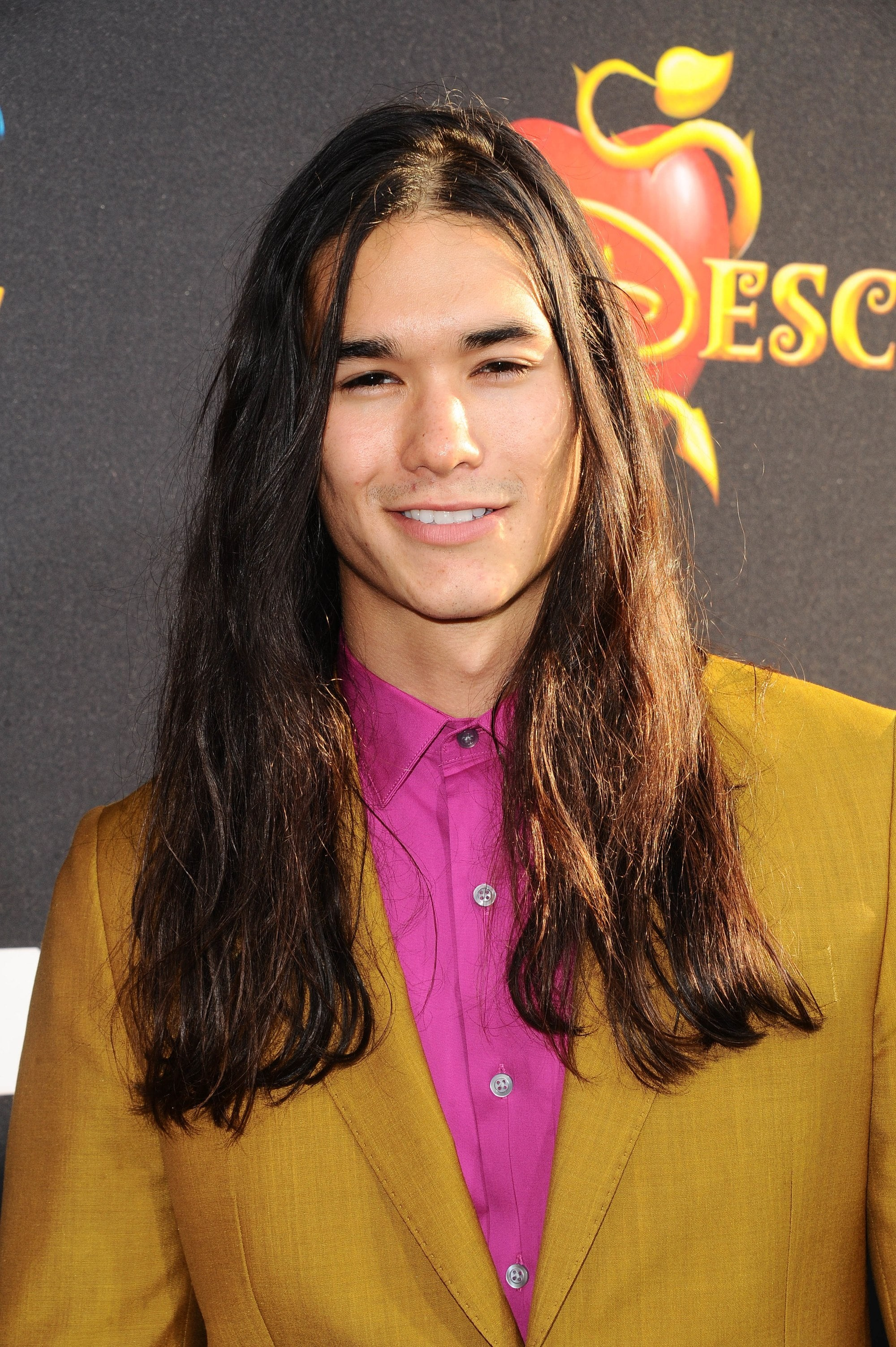 twilight actor booboo stewart on the red carpet with his long wavy dark hair wearing a pink shirt and mustard blazer