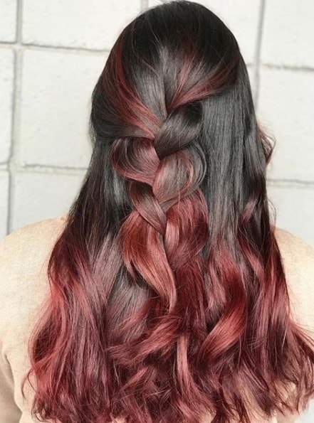 back view of a woman with long curly dark brown to cherry ombre hair styled in a half up half down braid