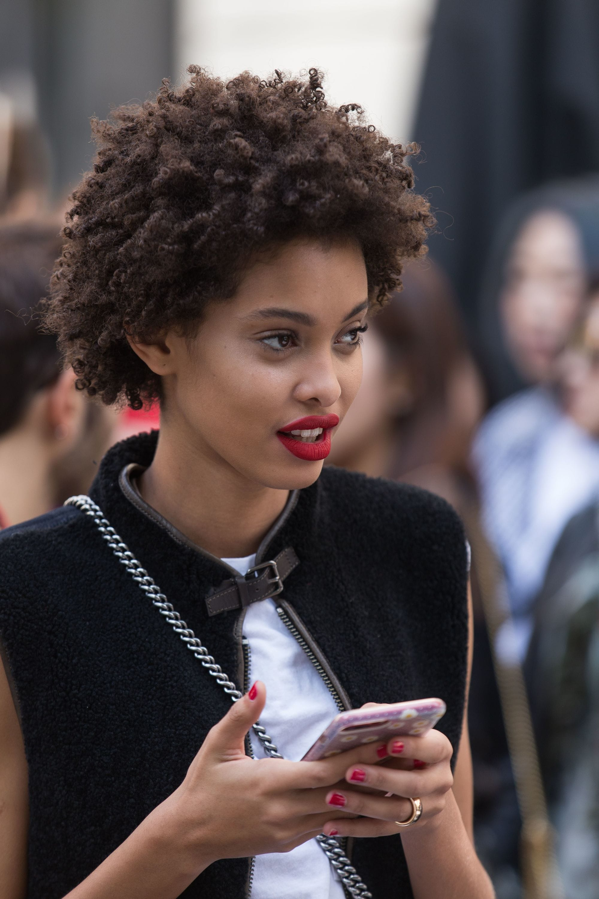 street style model with short brown afro hair wearing red lipstick holding her phone