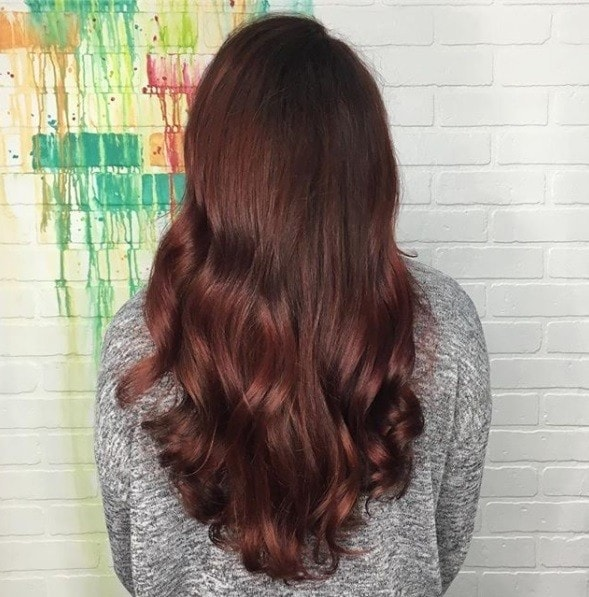 back view of a woman with long glossy cherry cola hair colour