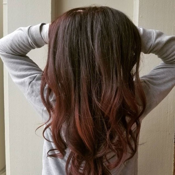 woman with long dark cherry ombre hair with her hands in her hair