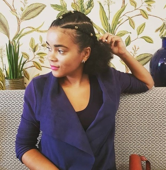 Protective hairstyles: Woman with natural hair in cornrows into a low ponytail with beads