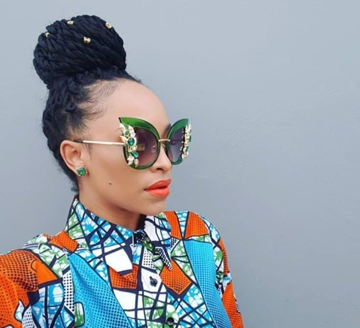 black hair dos: close up shot of woman with box twists, wearing floral african print top and sunglasses, posing against grey wall