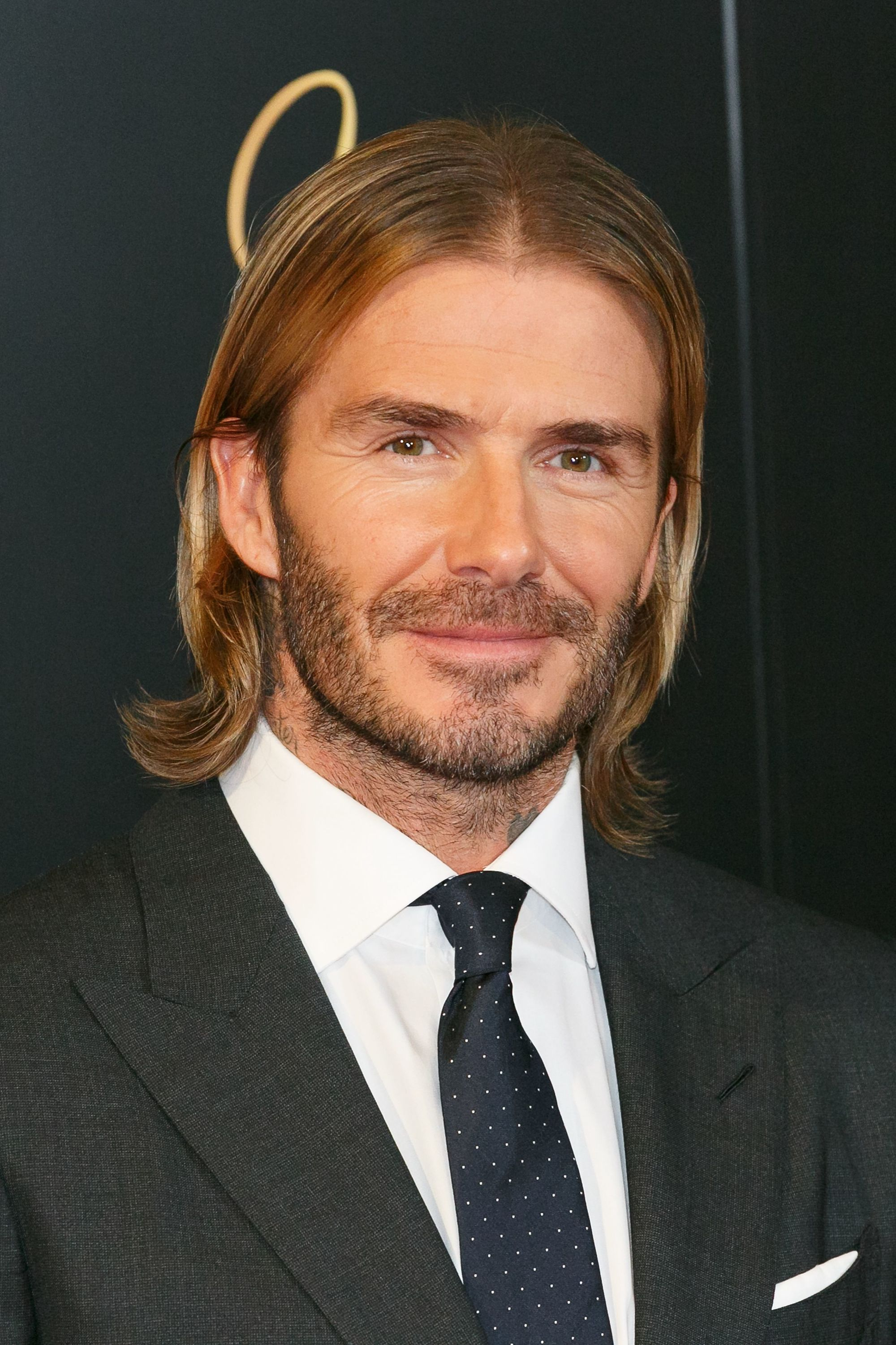 david beckham on the red carpet in a tux with slick long hair