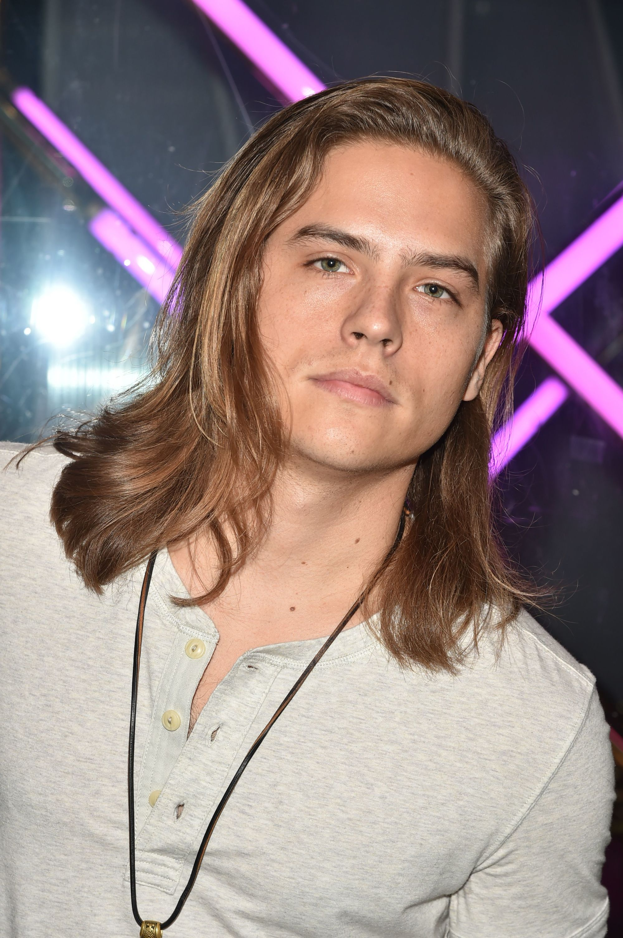 actor dylan sprouse with shoulder length layered dark blonde surfer hair