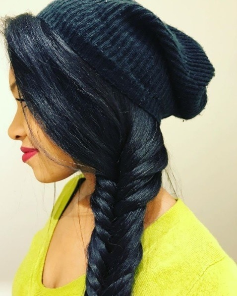 woman with long relaxed hair in a side fishtail braid with a beanie hat