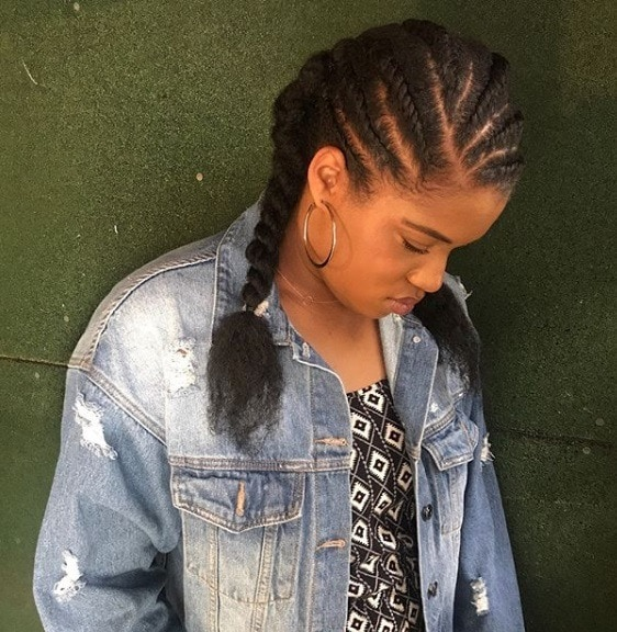 Protective hairstyles: Woman with her natural hair in flat twists into pigtails, wearing a floral top and denim jacket