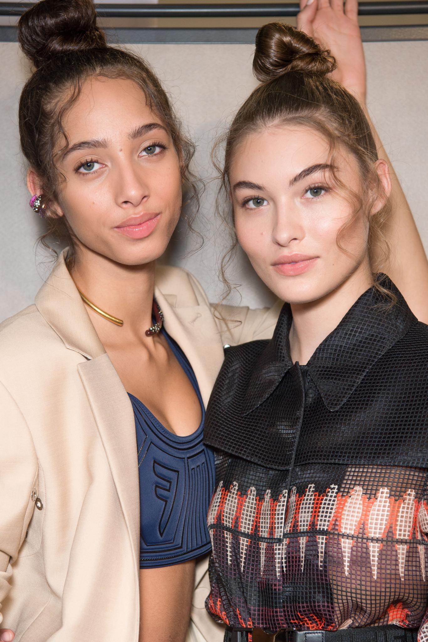Two models backstage at Fendi with wispy, flyaway hair styled into a topknot, wearing Fendi clothing and posing for picture