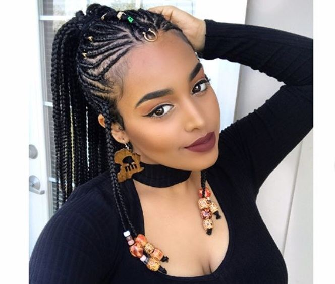 african hairstyles: close up shot of woman with fulani braids and beads pony hairstyle, wearing black cut out top and posing outside