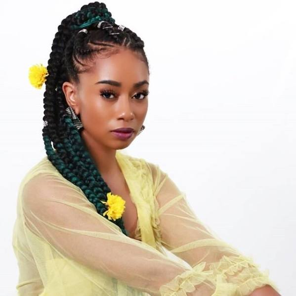 Protective hairstyles: Woman with her natural hair in a Ghana braid ponytail with yellow flowers in it