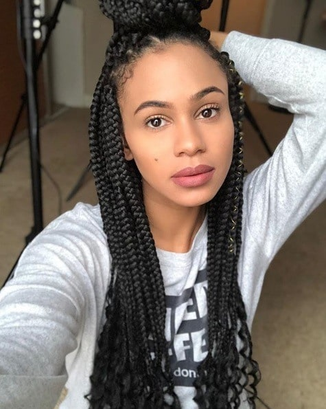 Protective hairstyles: Selfie of a woman with half up long Goddess braids with curly ends and yarn wraps