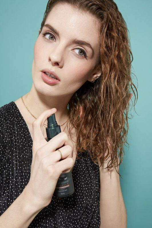 woman with shoulder-length brown-blonde curly hair using the Tresemme botanique hydrating mist
