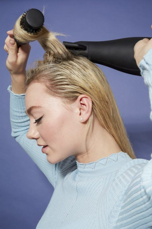 woman with medium length wet blonde hair wearing a light blue top, using a round brush and a hairdryer to style her hair