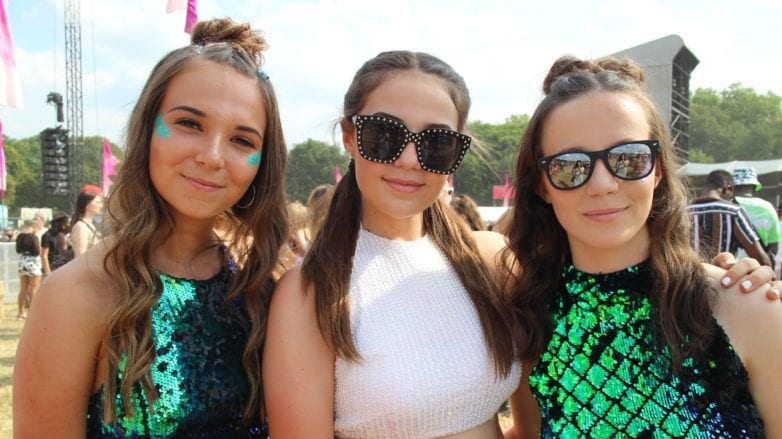 Festival hair must-haves: Three girls at Lovebox 2018 with brown hair styled in half-up, half-down braided bun s wearing green sequin dresses