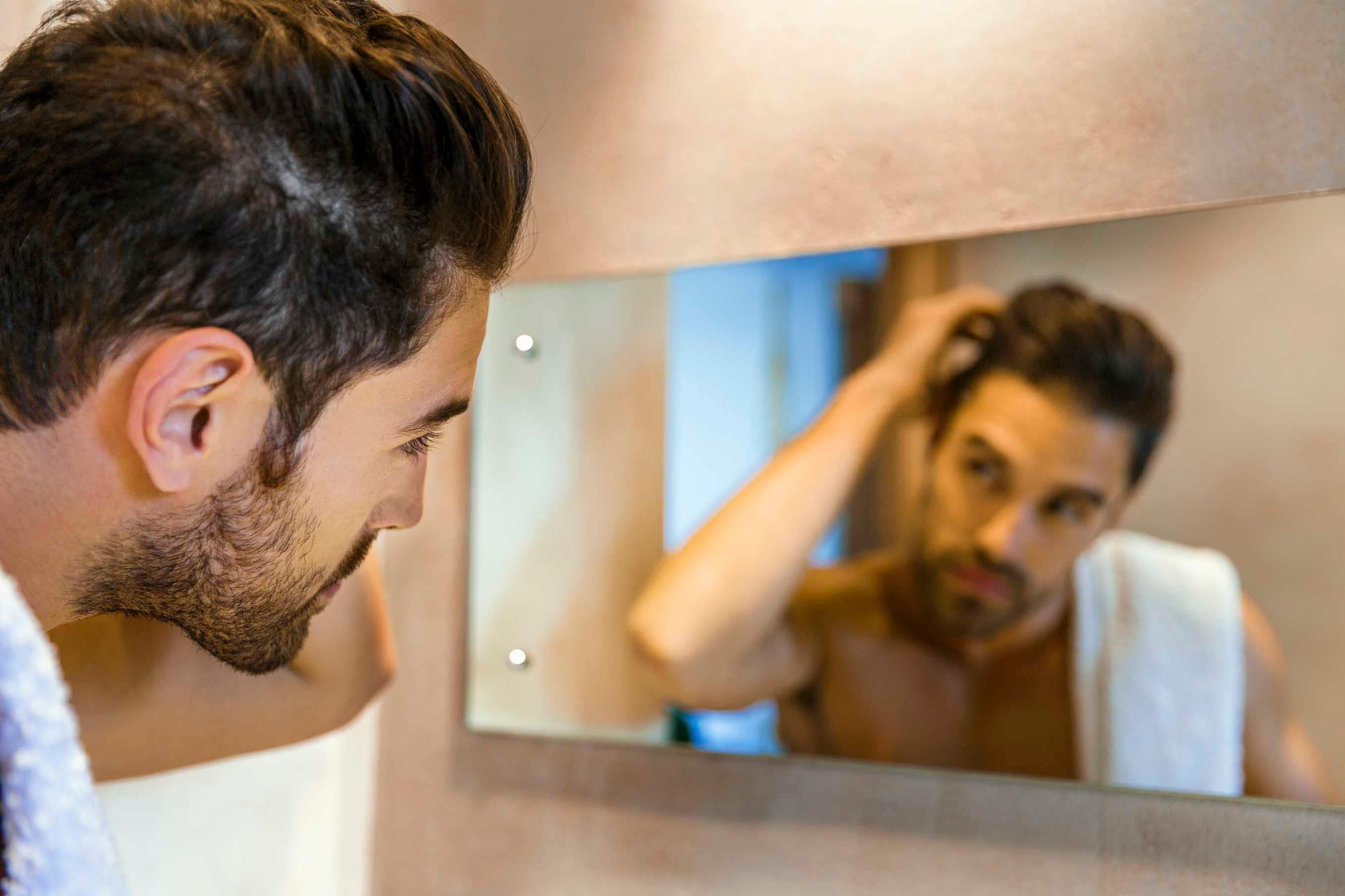 Male pattern baldness man looking in mirror with hand in hair