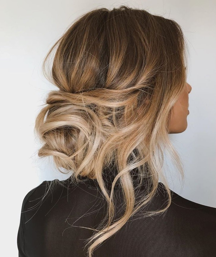 view from behind of a woman with bronde blondey brown hair in a curly bridal messy bun hairstyle