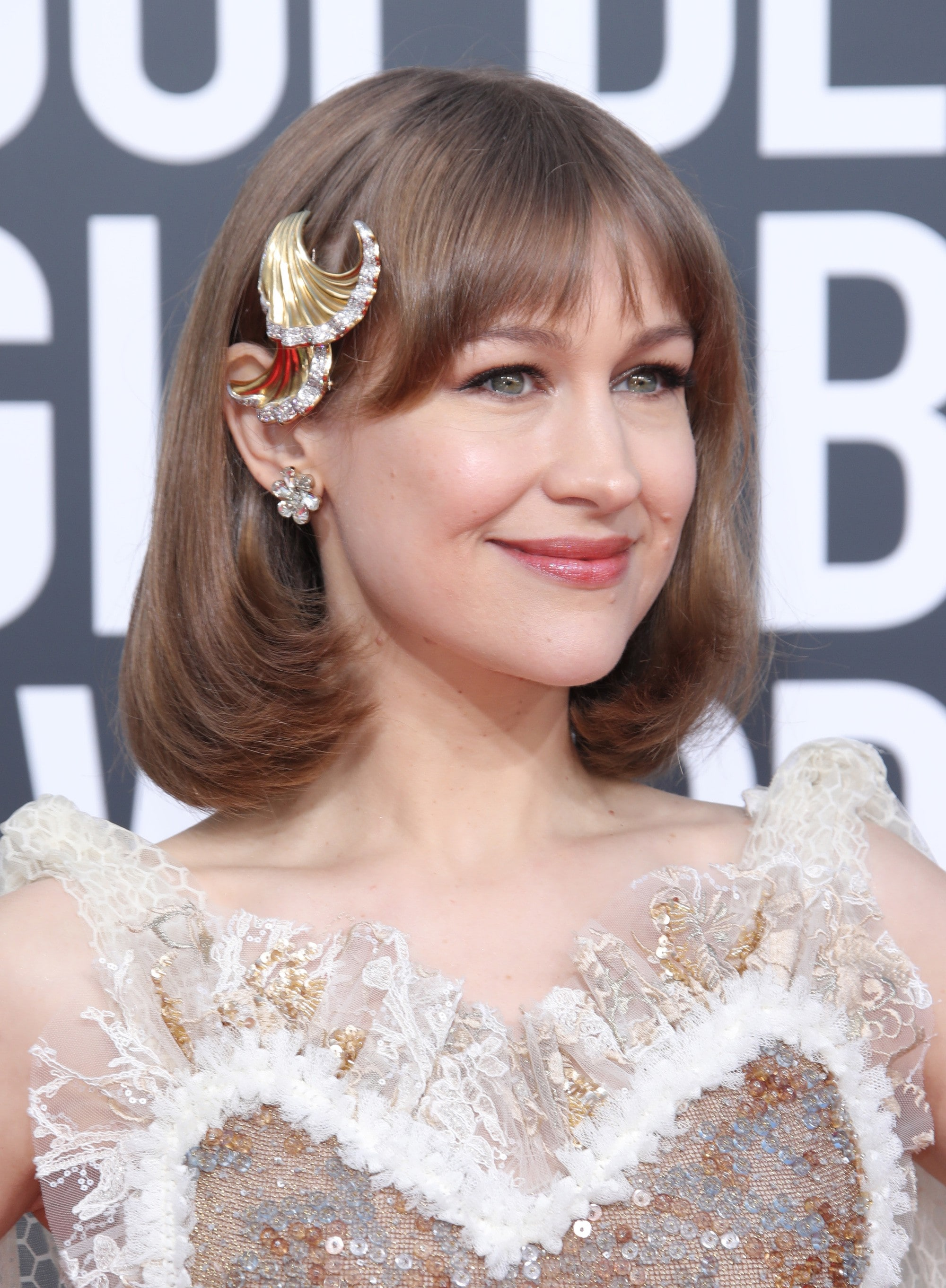 2019 Hair accessories: Joanna Newsom with a dirty blonde flipped long lob with a golden seashell hair accessory, wearing feathery dress and posing on the red carpet