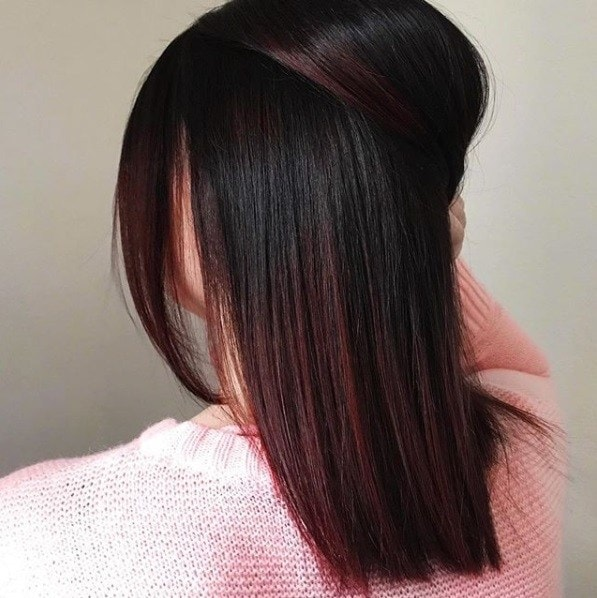 shot from behind of a woman with shoulder length straight dark brown and red ombre hair holding her hair in a half up style with her hand