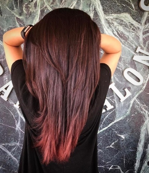 shot from behind of a woman with her hands in her long straight two tone cherry cola hair