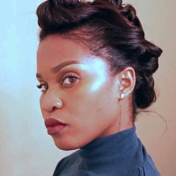 woman with relaxed hair styled into a vintage twist and pin updo hairstyle