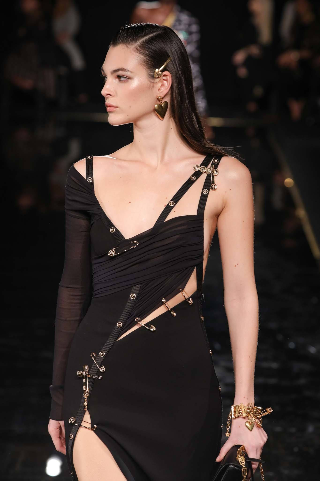 2019 Hair accessories: Model on the runway with dark brown hair with '90s hair slides in it, wearing all black on the Versace runway