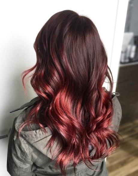 back view of a woman in a khaki jacket with vibrant curly cherry ombre hair
