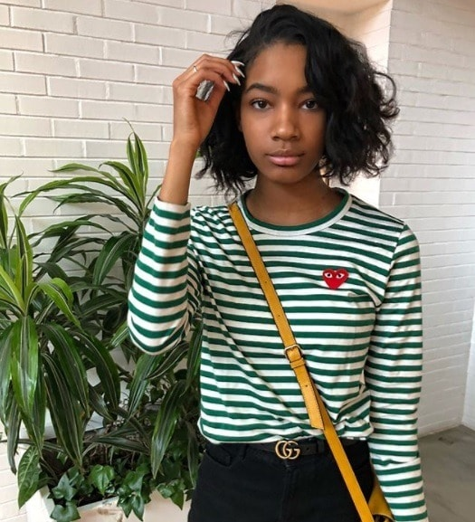 girl with short relaxed hair in a wavy french bob style, wearing a green striped commes des garcons tshirt
