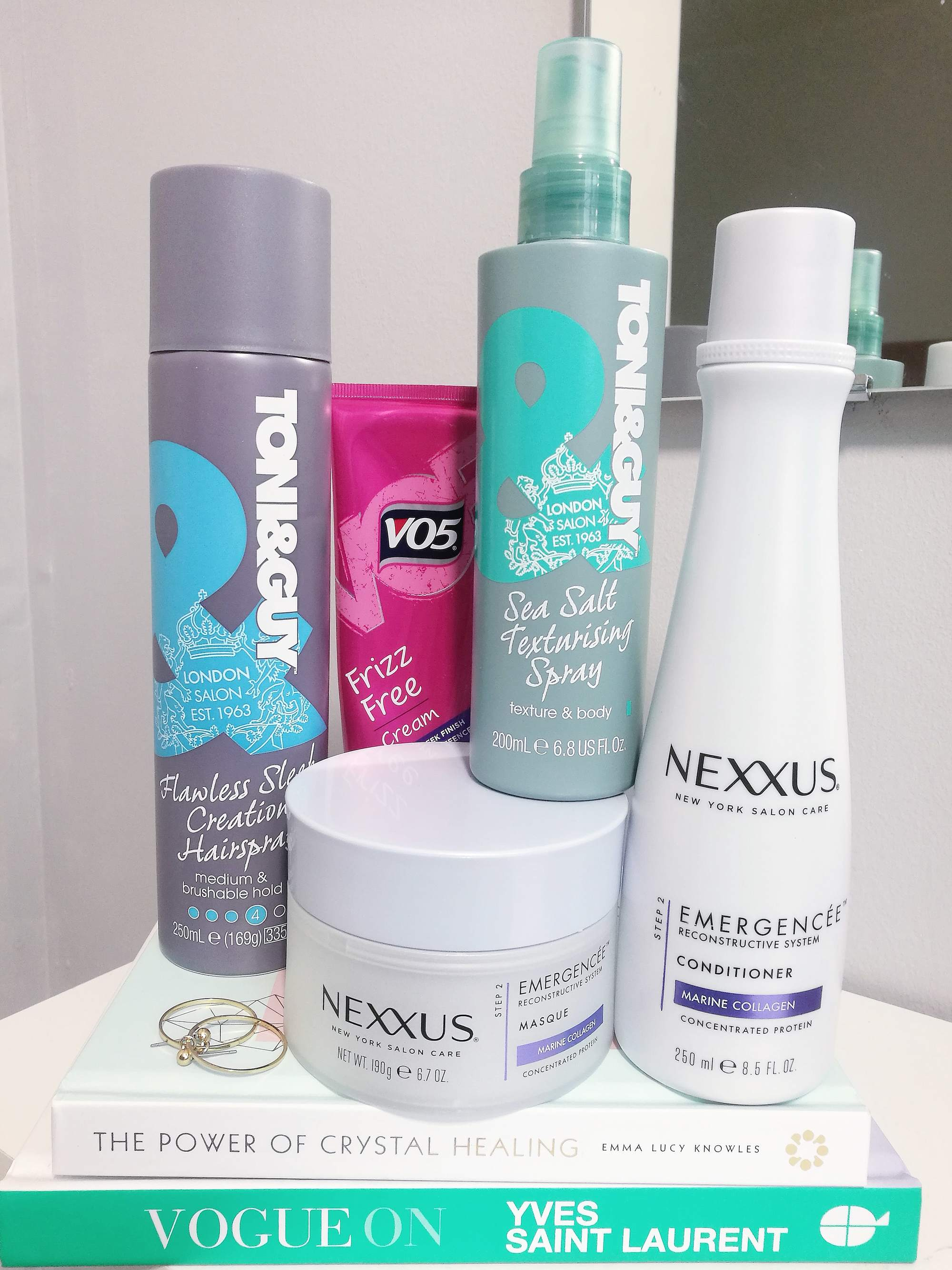 image of hair products on a stack of books, a toni and guy hairspray, vo5 frizz free cream, nexxus shampoo and mask, and a toni and guy sea salt spray