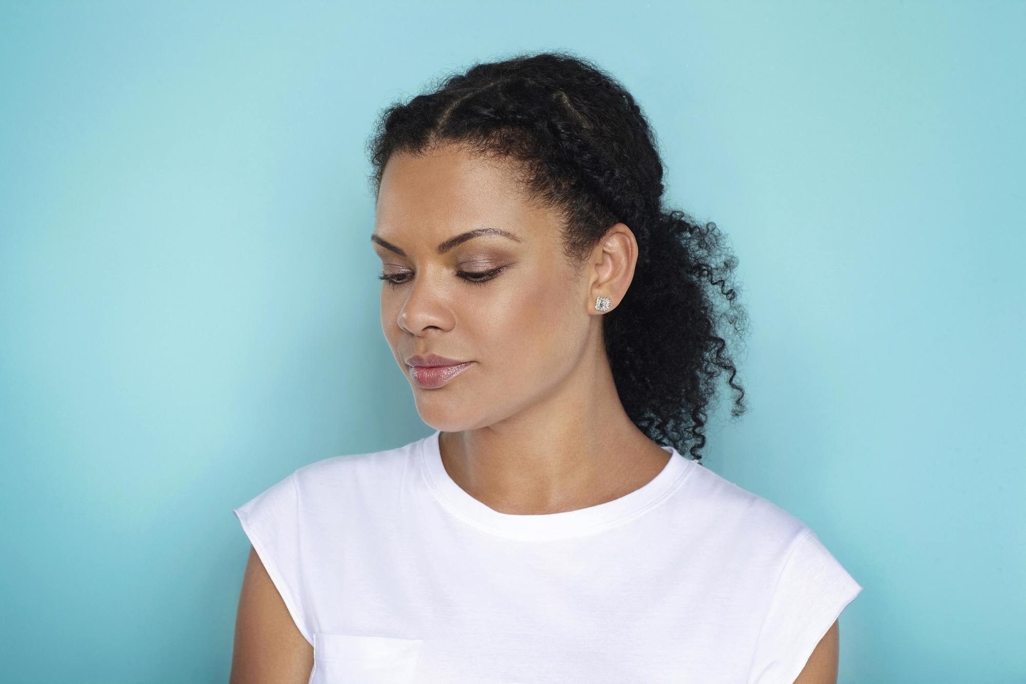 Easy natural hairstyles: Close up shot of woman with natural braided ponytail, wearing all white and posing in studio.