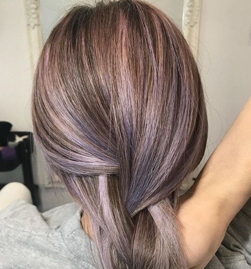 New hair colour trends: Back shot of woman with ash blonde hair with purple gem highlights, wearing blue.