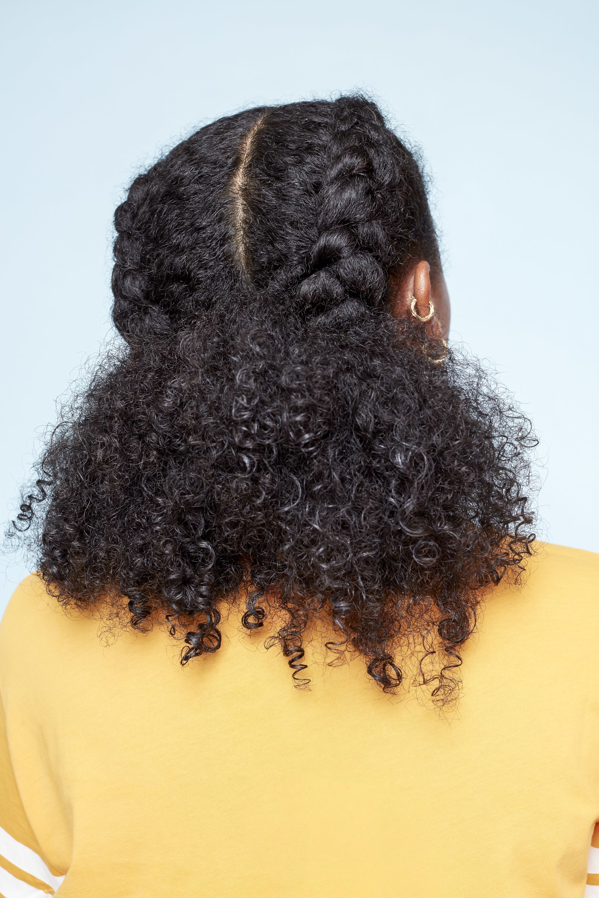 Easy natural hairstyles: Back shot of a model with dark brown shoulder-length natural hair styled into a Dutch braids ponytail, wearing a yellow top and posing in a studio setting.