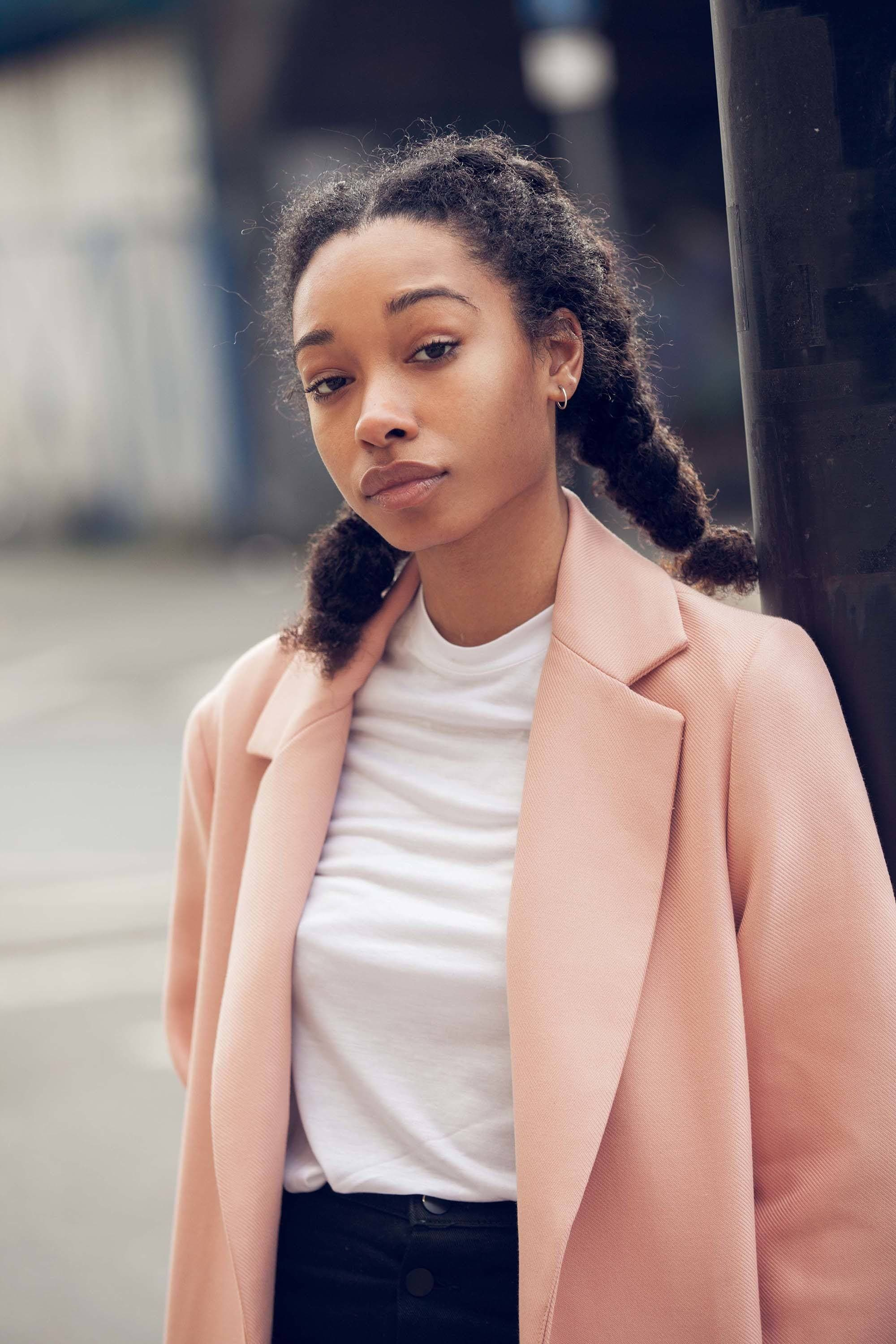 Easy natural hairstyles: Close up shot of street style model with natural hair styled it into flat twist pigtails, wearing pink jacket with white tee and black jeans.