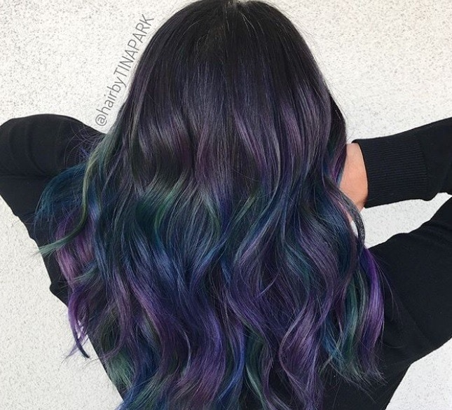 New hair colour trends: Back shot of a woman with long, curly dark brown hair with oil slick highlights in it.