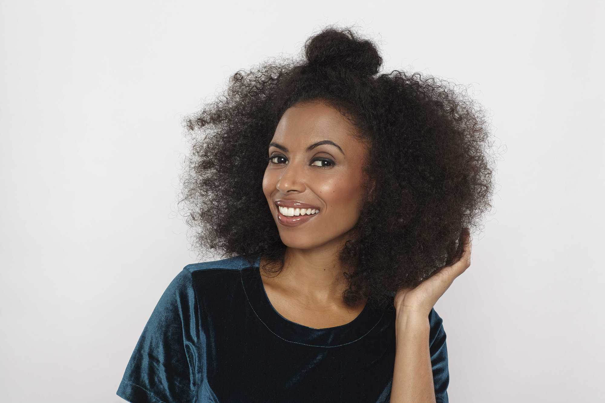 Easy natural hairstyles: Close up shot of model with natural hair styled into a half up half down bun hairstyle, wearing velvet top and posing in a studio.