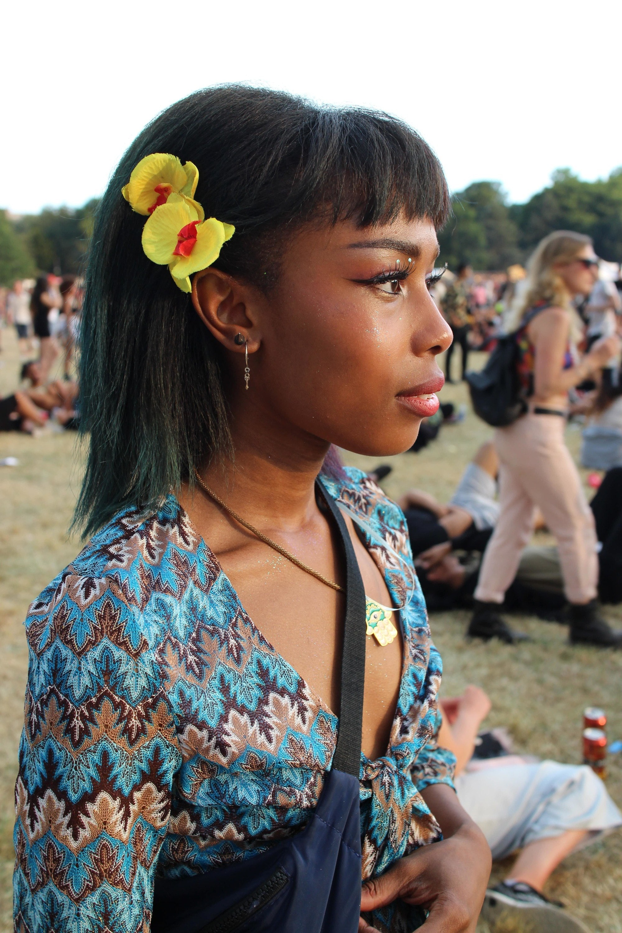 Floral festival hair: side view of black woman with straight dark brown hair at festival with yellow sunflower hairclips positioned on the side of her just behind her fringe. Girl is wearing a blue patterned top and side bag.