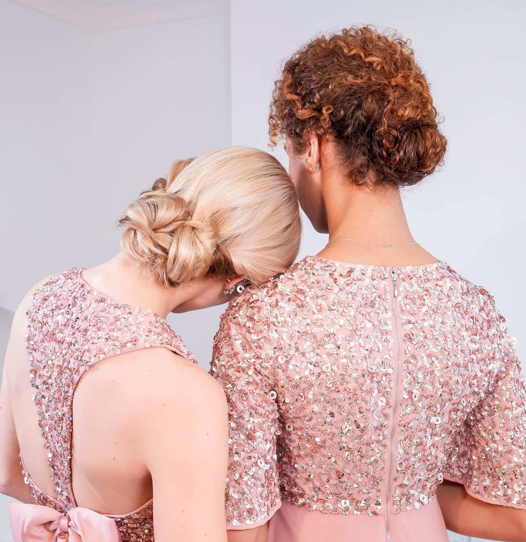 Easy natural hairstyles: Close up shot of two models with low braided buns, wearing pink formal dresses and posing for an editorial shoot.