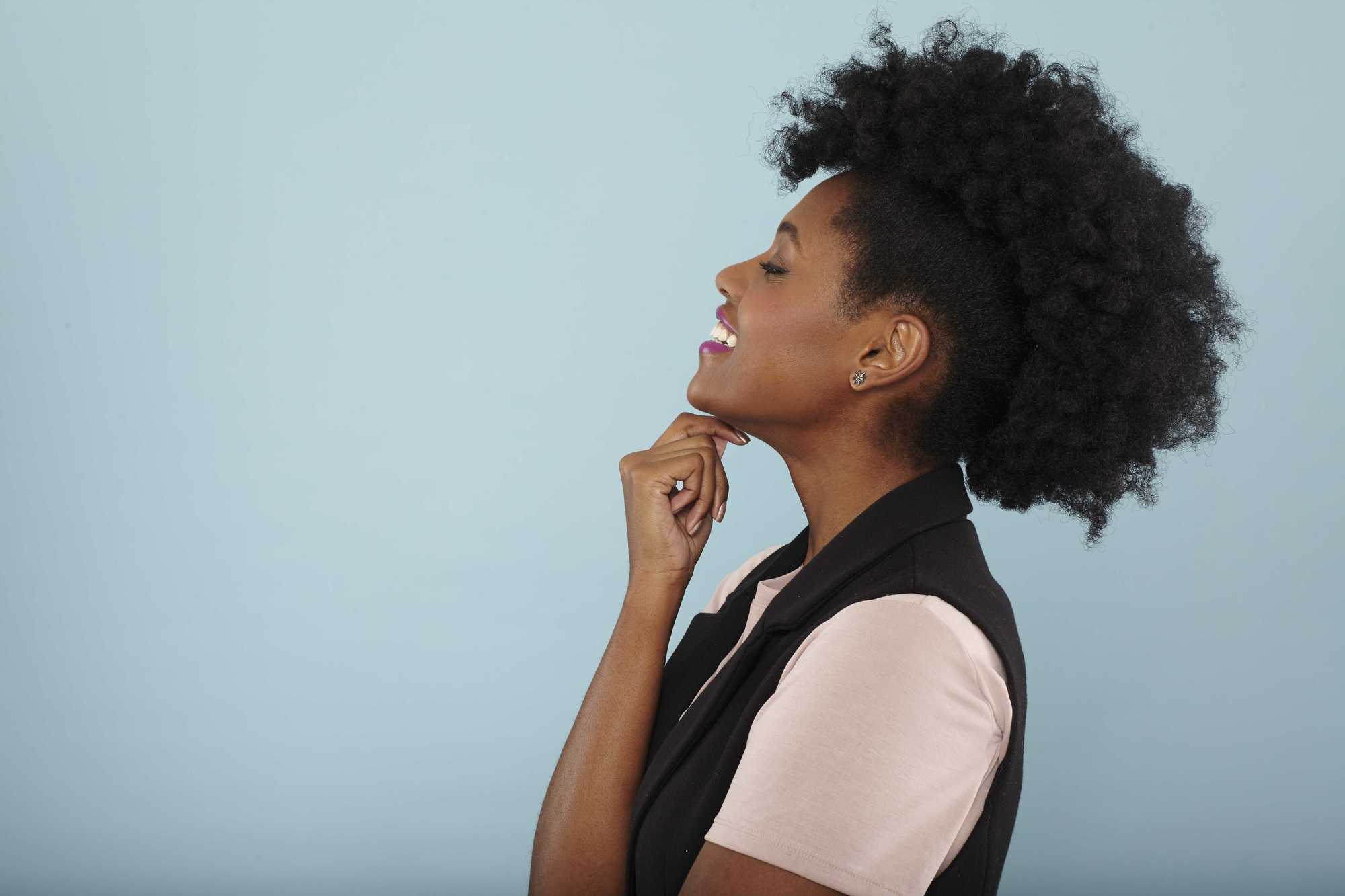 Easy natural hairstyles: Close up shot of model with natural hair frohawk hairstyle, wearing black and white top posing in a studio.