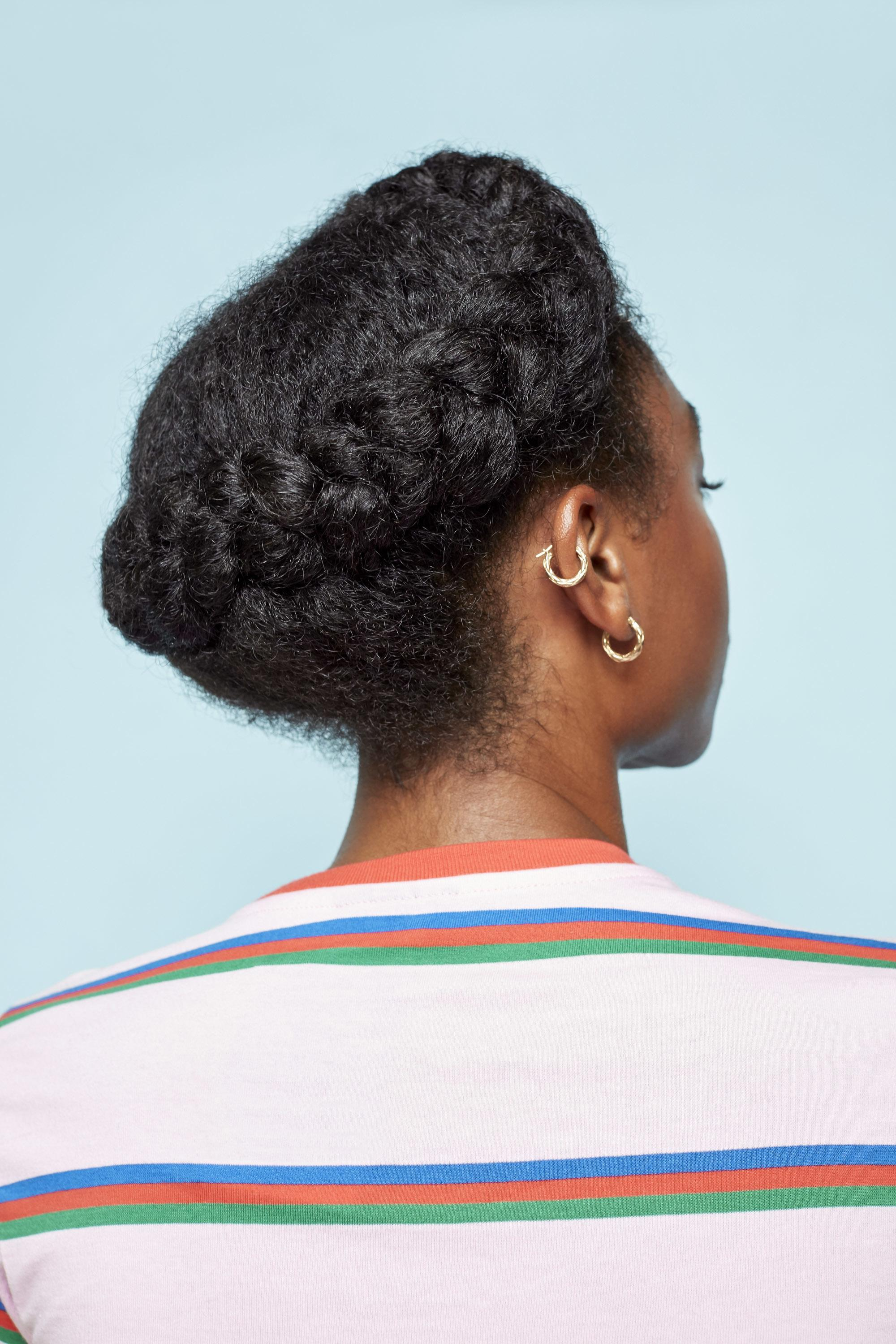 Easy natural hairstyles: Back shot of a model with dark brown natural hair styled into a halo braid, wearing a striped top and posing in a studio.