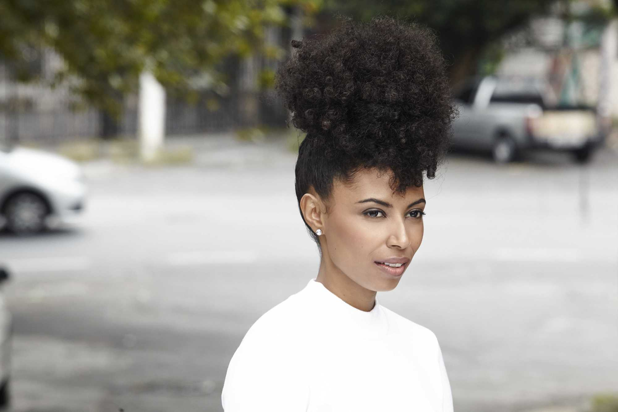 easy natural hairstyles: close up shot of woman with natural hair styled into a pineapple updo