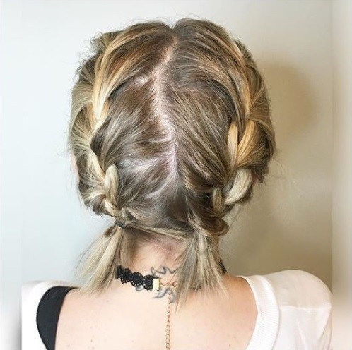 Easy braids for short hair: Back view of short blonde hair in two French braided pigtails.