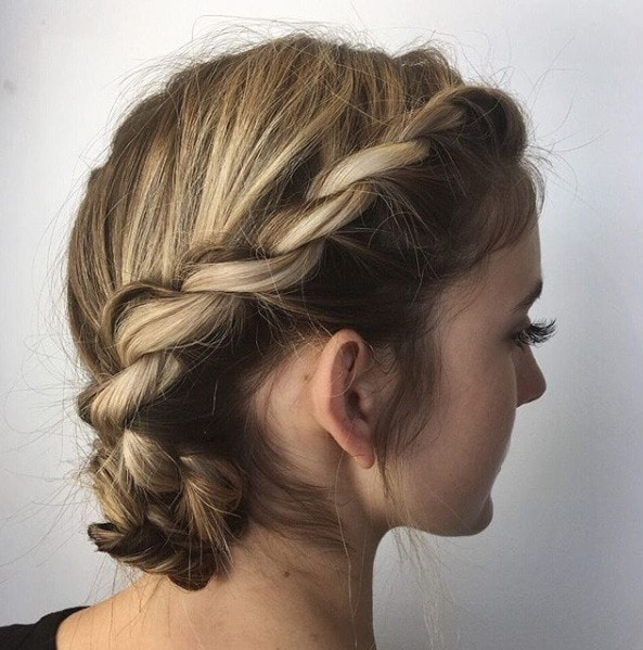 Easy braids for short hair: Side profile of a woman with dark blonde hair styled in a twisted braided bun.