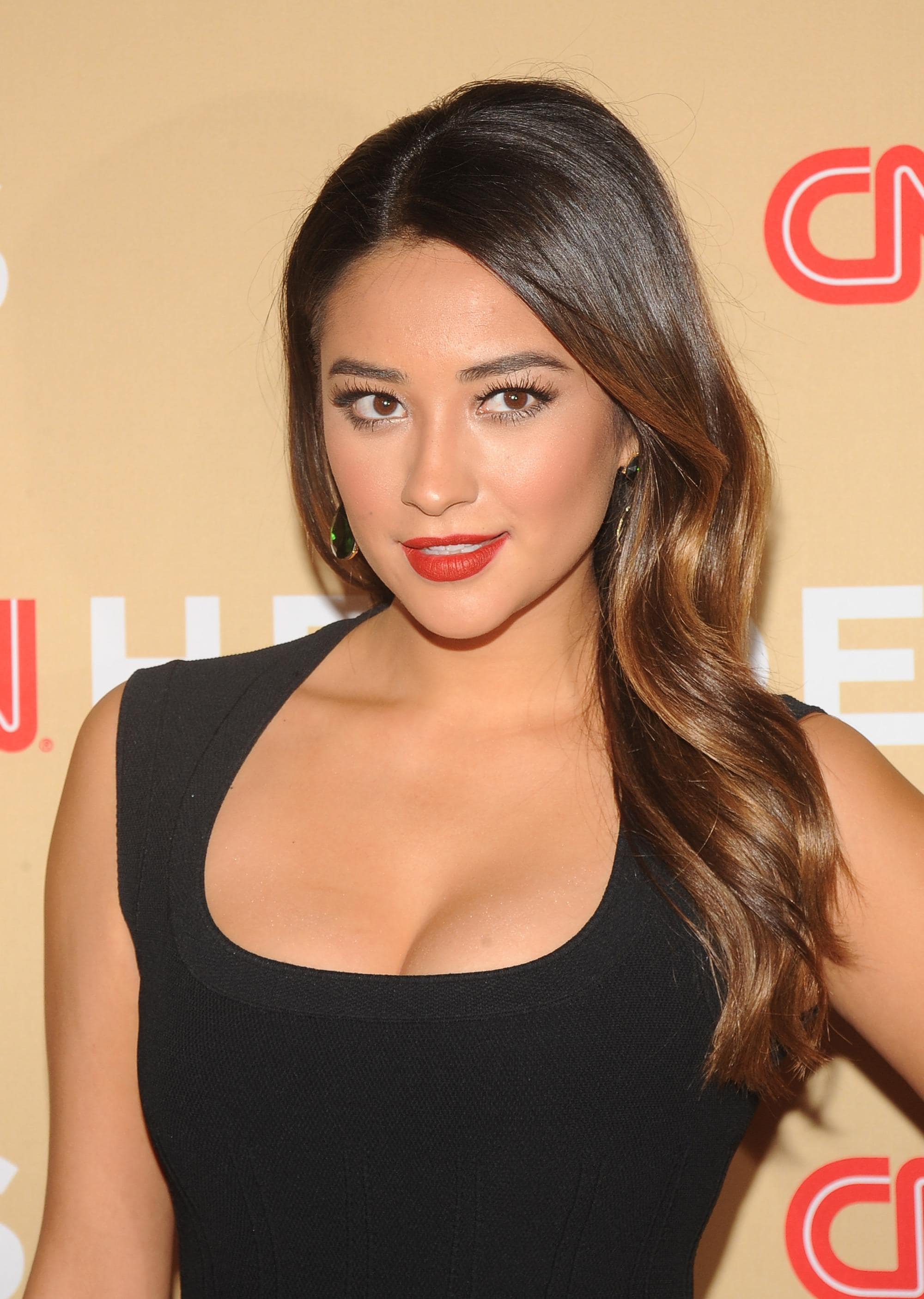 shay mitchell with long sideswept curls in caramel and chocolate brunette with lowlights