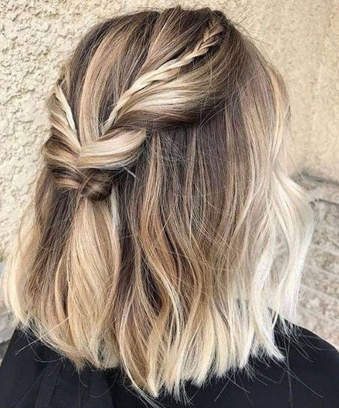 Easy braids for short hair: Back view of a woman with ash blonde hair in a half up twisted with small braided details